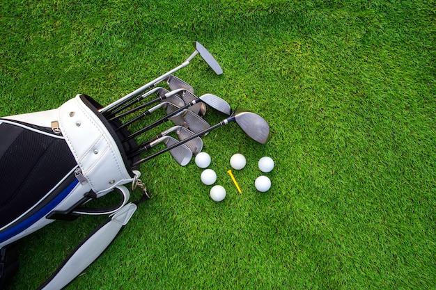 Pelota de golf y club de golf en bolsa sobre hierba verde