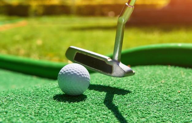 Pelota de golf y club de golf sobre césped artificial.