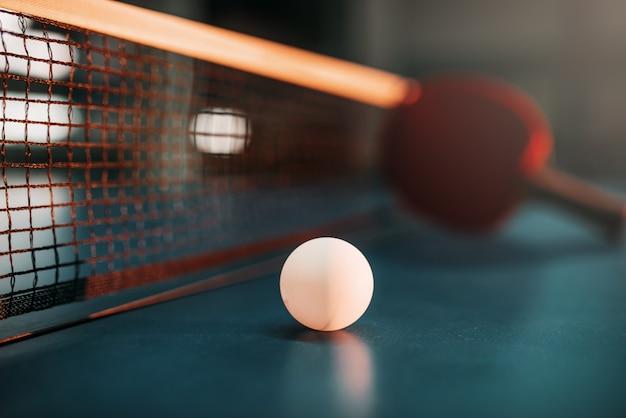 Pelota de ping pong sobre la mesa contra la red, el enfoque selectivo, la raqueta