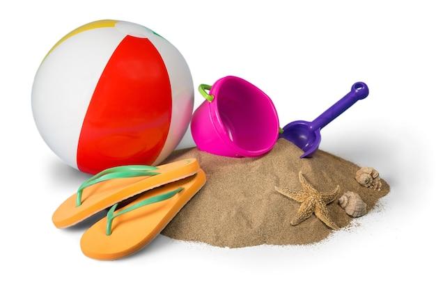 Pelota de playa, juguetes y chanclas sobre arena aislado en blanco