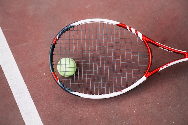 Pelota de tenis de alto ángulo con raqueta al lado