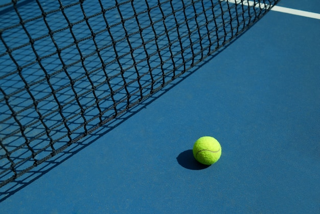 La pelota de tenis amarilla está tendida cerca de la red negra de la cancha de tenis abierta.
