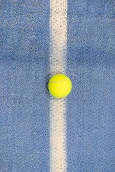 Pelota de tenis cubierta en cancha de tenis, línea blanca, superficie azul, espacio de copia