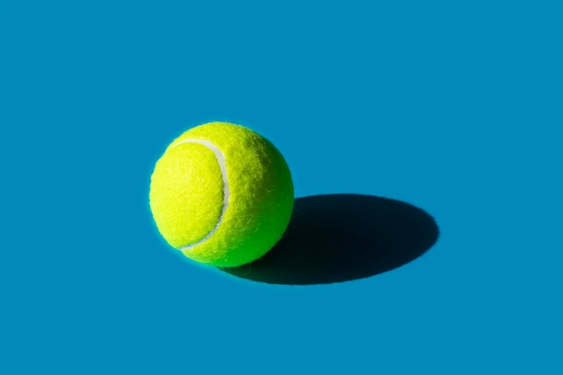 Pelota de tenis con fuerte sombra sobre fondo azul.