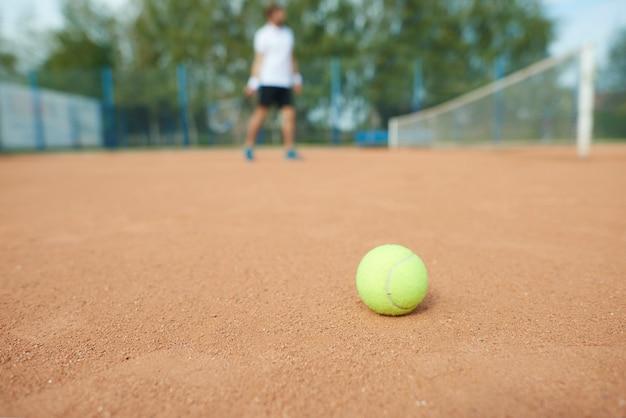 Pelota de tenis y hombre en la cancha de tenis