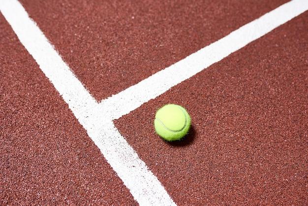 Pelota de tenis en el piso de la cancha