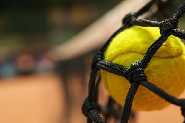 Pelota de tenis en red, cierre y espacio para texto