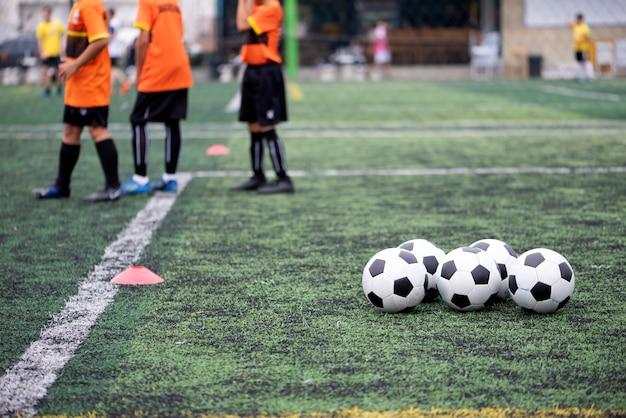 Pelotas de entrenamiento en campo de fútbol verde