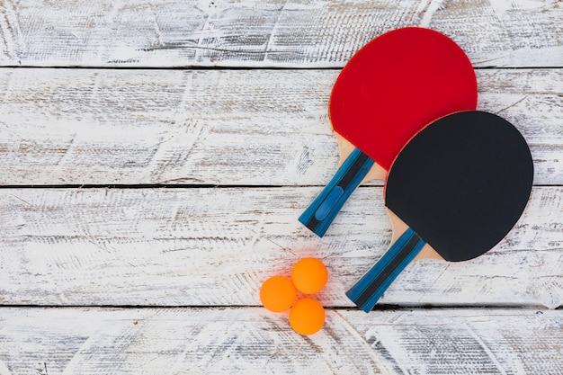 Pelotas de ping pong y raqueta de madera sobre fondo blanco de madera