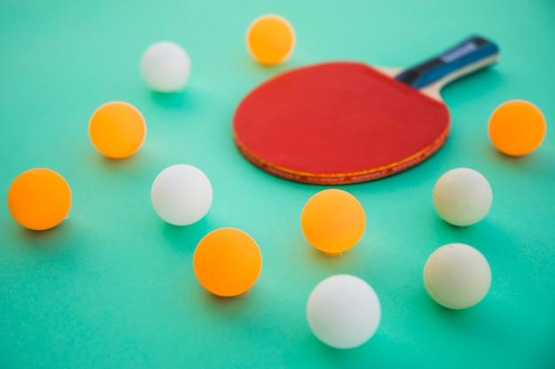 Pelotas de ping pong y raqueta de madera sobre fondo turquesa.