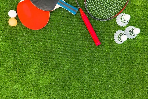Pelotas de ping-pong; volantes; bádminton y raquetas sobre césped verde.