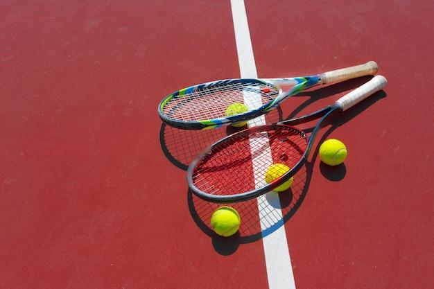 Pelotas de tenis y raqueta en la cancha de césped