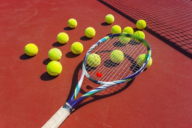 Pelotas de tenis y raqueta en la cancha de césped.