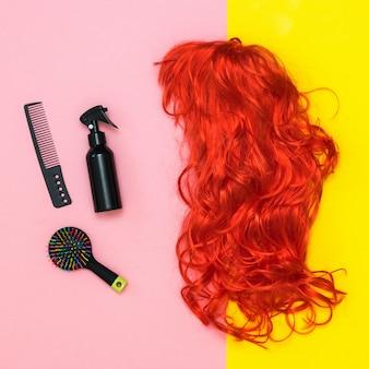 Peluca brillante, tijeras y peine sobre fondo rosa y amarillo. estilo de vida. accesorios para crear estilo.