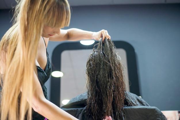 Una peluquera en acción cortando el pelo largo.