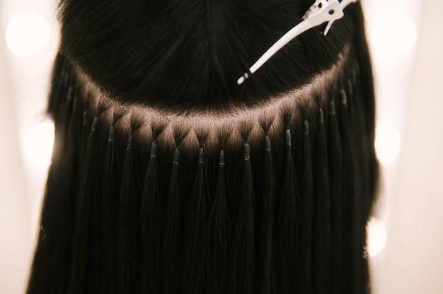 La peluquera le hace extensiones de cabello a una joven en un salón de belleza.