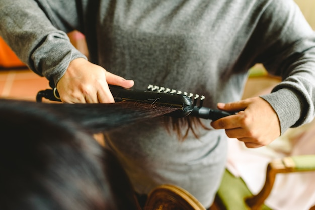 Peluquería alisando los cabellos oscuros de un cliente.