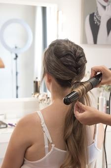 Peluquería alisar el cabello con una plancha al cliente. sesión de peluquería.