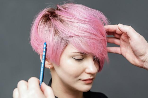 Peluquería comprobando el cabello rosado femenino