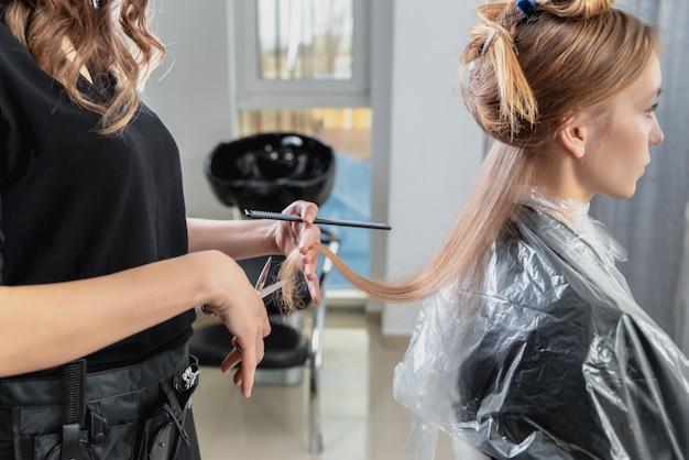 Peluquería corta el cabello de una joven rubia en peluquería