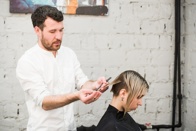 Peluquería corta el cabello con unas tijeras en la corona de un cliente guapo y satisfecho en una peluquería profesional.