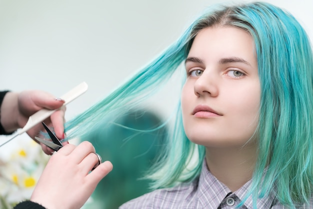 Peluquería de corte con tijeras de pelo largo verde de mujer joven. cuidado del cabello en salón de belleza profesional.