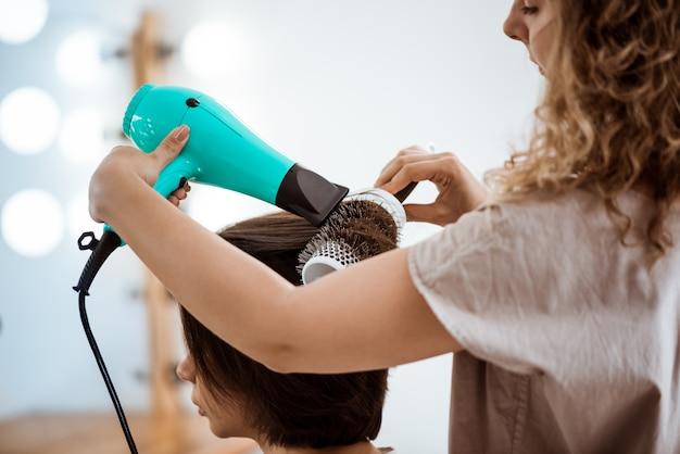 Peluquería femenina haciendo peinado a mujer morena en salón de belleza