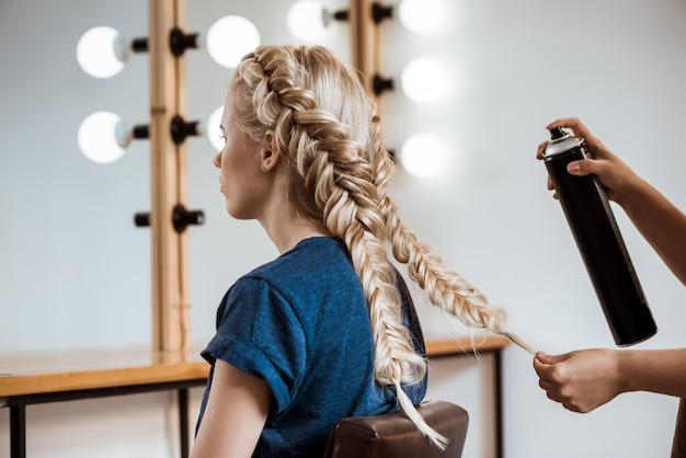 Peluquería femenina haciendo peinado a mujer rubia en salón de belleza