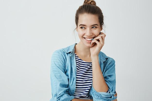 Peluquería femenina pasar un buen rato en el trabajo. foto de estudio de atractiva mujer moderna en peinado de bollo con los dedos cerca de los labios y sonriendo ampliamente mientras mira a un lado, hablando con un compañero de trabajo