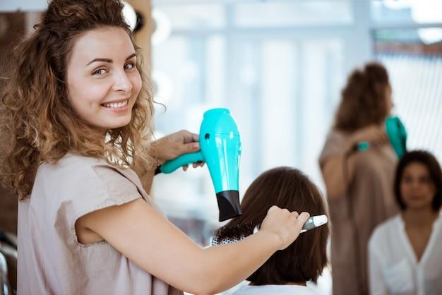 Peluquería femenina sonriendo, haciendo peinado a mujer en salón de belleza