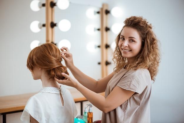 Peluquería femenina sonriendo haciendo peinado a pelirroja mujer en salón de belleza