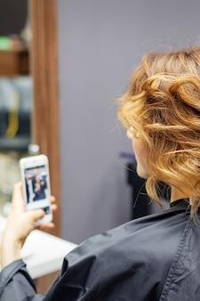 Peluquería haciendo peinado para mujer joven con pelo rizado rojo y con smartphone en sus manos en salón de belleza
