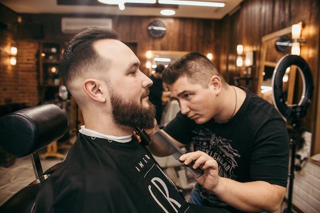 Peluquería, un hombre con barba cortada de peluquería. corte de pelo profesional, peinado retro y peinado. hermoso cabello y cuidado, peluquería para hombres. servicio al cliente.