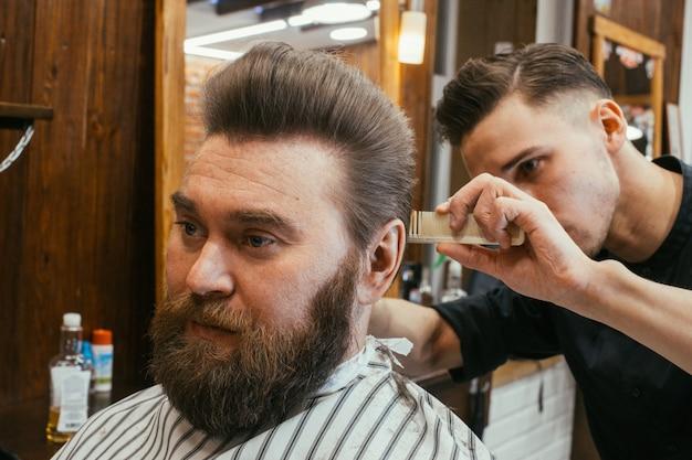 Peluquería, un hombre con barba cortada de peluquería. hermoso cabello y cuidado, peluquería para hombres