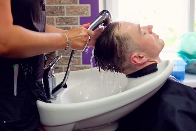 Peluquería lavando el cabello al joven