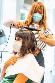 Peluquería con máscara y cliente, comenzando el peinado ondulado. reapertura con medidas de seguridad para peluqueros en la pandemia de covid-19. nuevo normal, coronavirus, distancia social