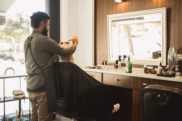 Peluquería masculina peinando cabello de cliente senior