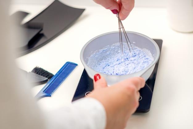Peluquería está mezclando tinte en un tazón blanco para teñir el cabello en sus manos