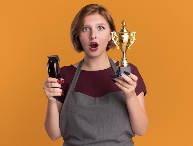 Peluquería de mujer hermosa joven en delantal con máquina recortadora y trofeo de oro mirando al frente sorprendido y asombrado de pie sobre la pared naranja