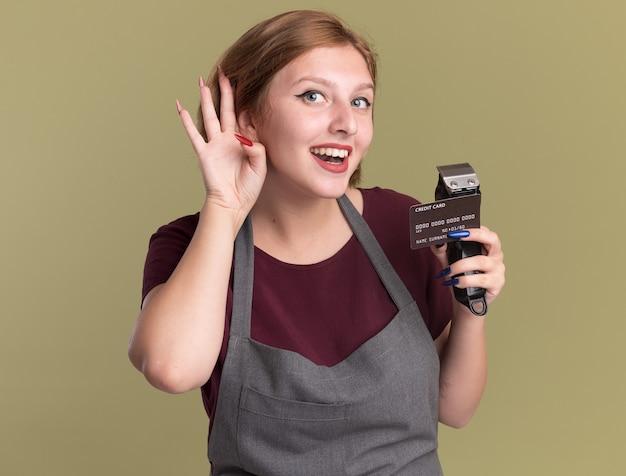 Peluquería de mujer hermosa joven en delantal con recortador y tarjeta de crédito con la mano sobre la oreja tratando de escuchar los chismes de pie sobre la pared verde