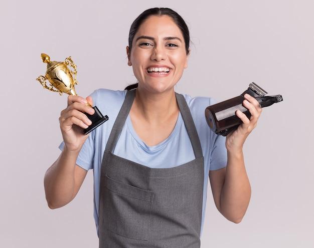 Peluquería de mujer hermosa joven feliz en delantal con máquina recortadora de trofeo de oro con botella de spray mirando al frente con una sonrisa en la cara de pie sobre la pared blanca