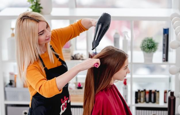 Peluquería mujer rubia seca el cabello largo del cliente joven con secador de pelo en el salón