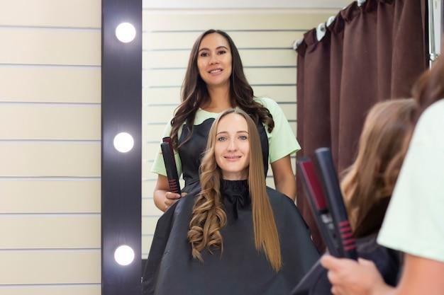 Peluquería de mujeres, salón de belleza. peluquero hace rizos con un rizador