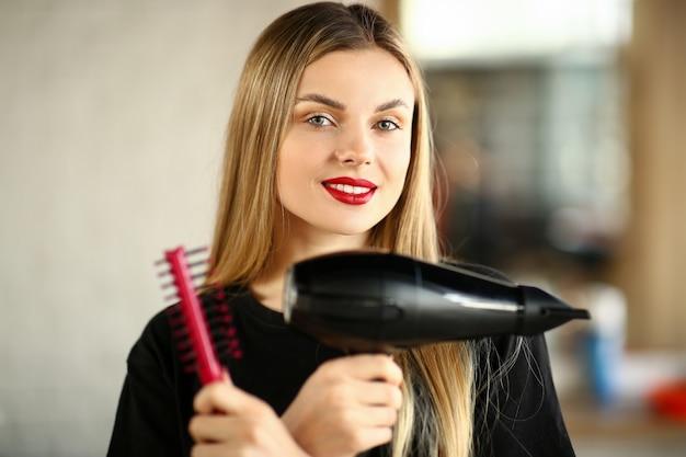 Peluquería niña cruzó las manos con peine y secador. hermosa estilista con cepillo y secador de pelo para peinar.