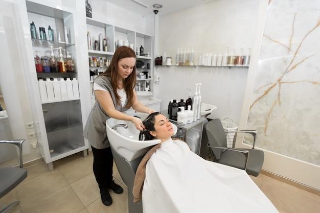 Peluquería de niña lava su cabello con champú y masajea la cabeza de una mujer joven en un salón de peluquería moderno