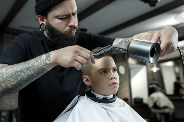 Peluquería de niños cortando a niño en una barbería