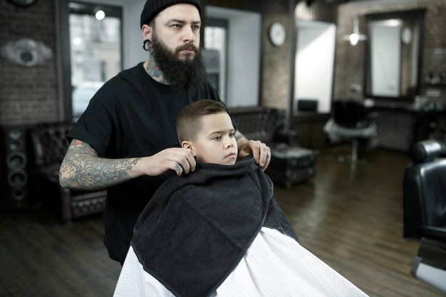 Peluquería de niños cortando a niño pequeño contra un fondo oscuro.