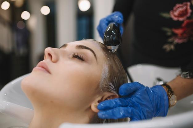 Peluquería que lava la cabeza del cliente después de teñir