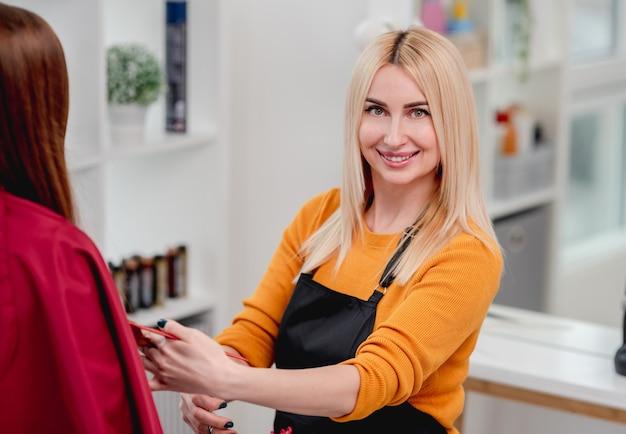 Peluquería rubia atractiva mirando al frente y sonriendo durante el proceso de corte de pelo