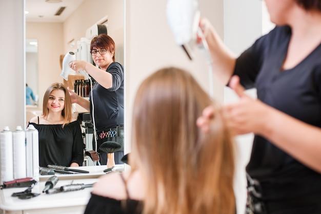 Peluquería seca el cabello con secador de pelo en salón de belleza.